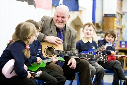 Headteacher Geoff Smith sat with pupils during music lesson.